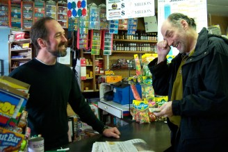 General store owner and a customer share a laugh.