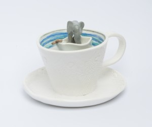 Storm in a teacup. Stoneware elephant in a boat in a porcelain teacup.