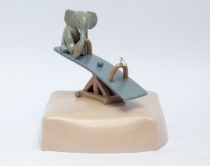 The Power of posiought. Stoneware elephant on a seesaw with a porcelain butterfly. Stoneware.