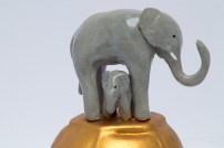 Mother and Child. Stoneware elephant on a gold pained podium.