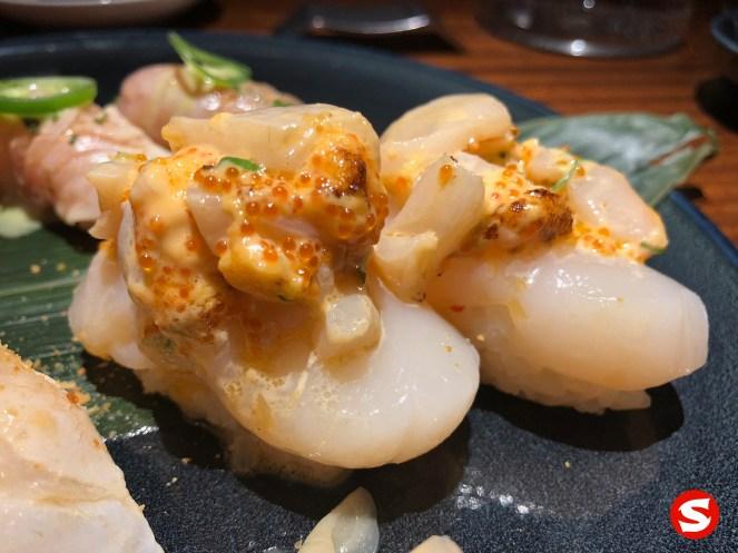 hotategai (scallop) nigiri with seared ibodai (butterfish) and ikura (salmon roe) topping