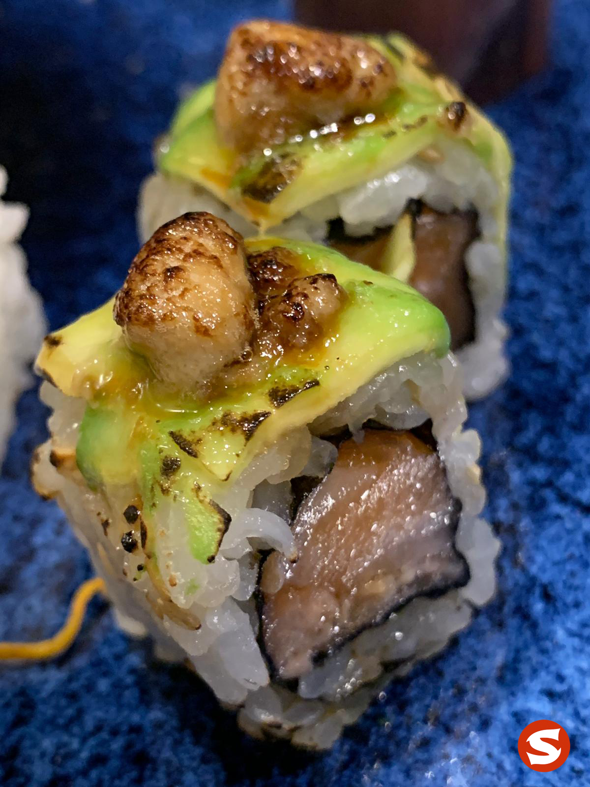 sake (salmon) uramaki (inside out roll) with avocado & hotategai (scallop) topping
