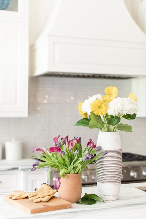 2 vases of cut fresh flowers in kitchen