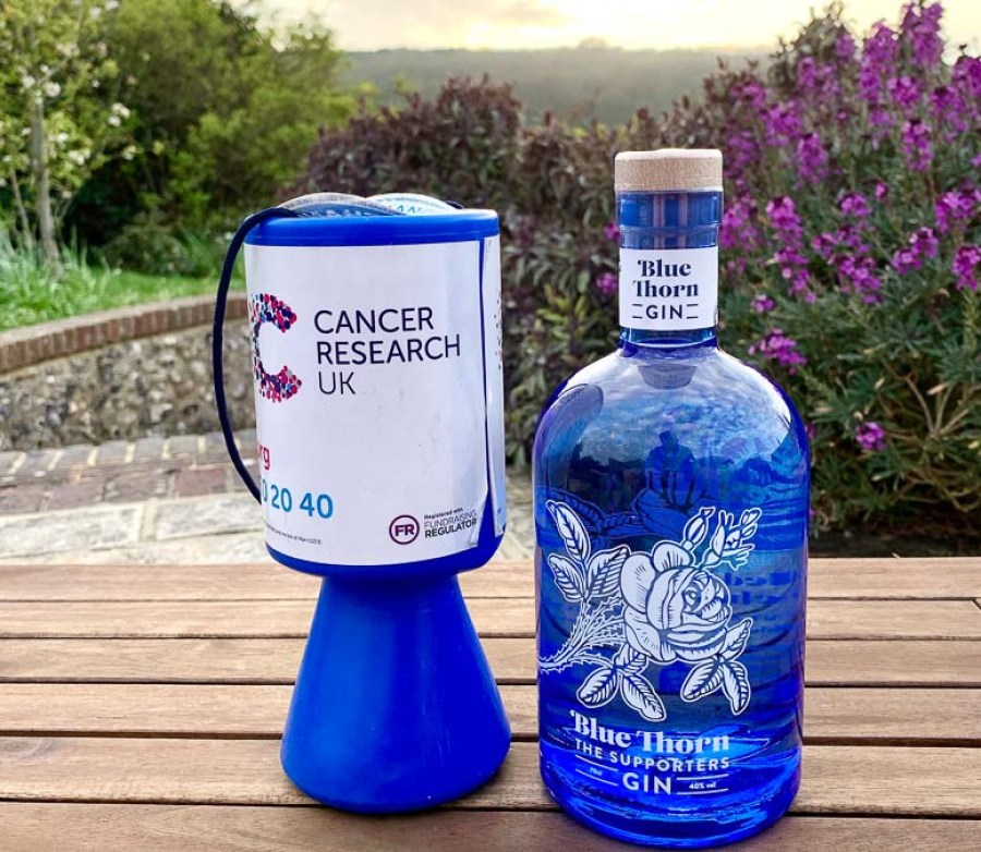 Bottle of Blue Thorn Gin next to Cancer Research Collecting tin