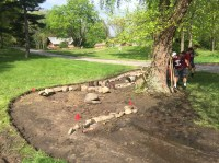 Glacial stone placed in a way to help slow water through the rain garden.
