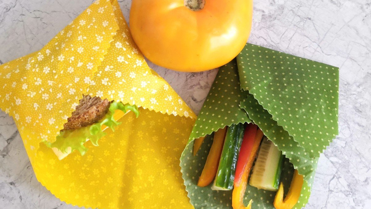 Sandwich, cucumber and bell pepper wrapped in yellow and green beeswax wraps on a counter