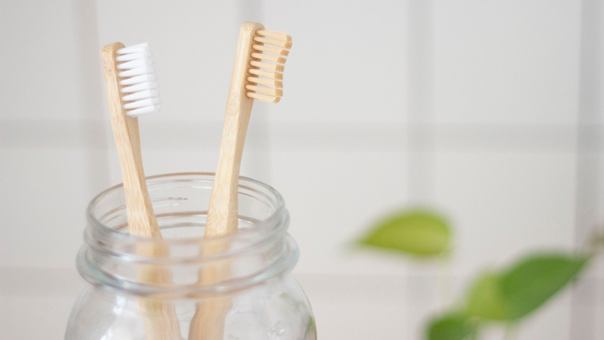 two bamboo toothbrushes in a glass jar