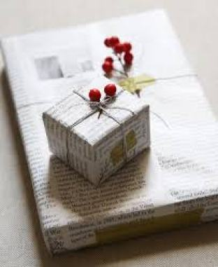 Photo of a gift wrapped in newspaper, tied with jute and decorated with fresh plants from the garden.