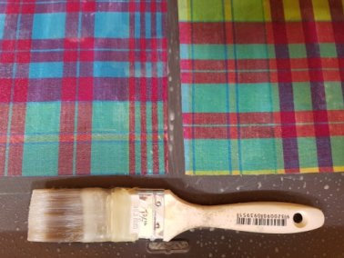 Photo of prepared fabric on a baking tray next to a paint brush.