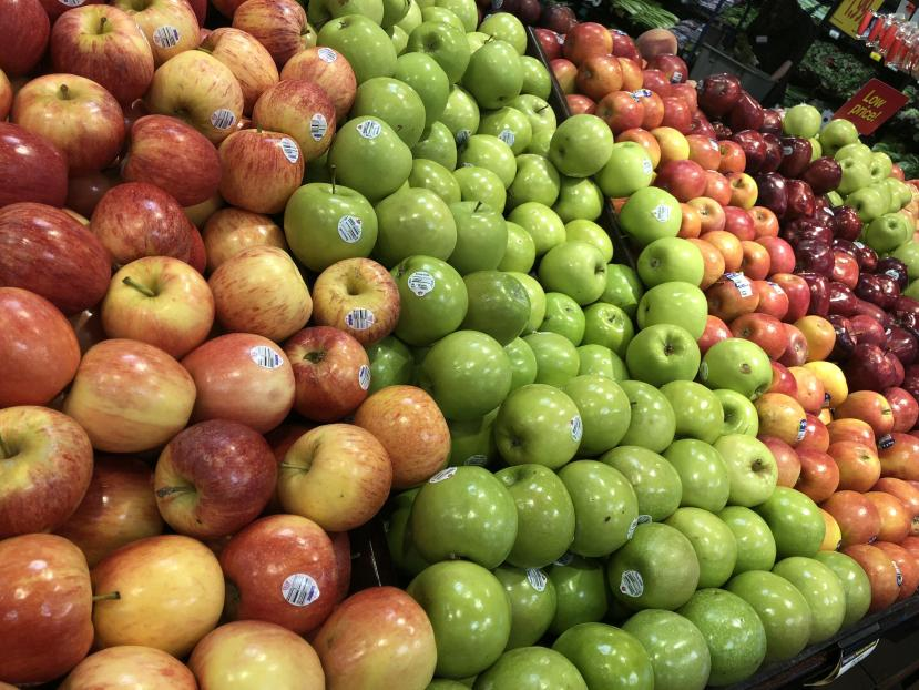 assortment of apples displayed at grocery store