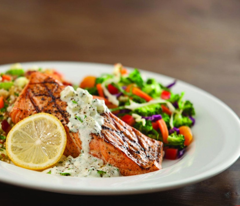 Salmon with sauce and vegetables on white plate