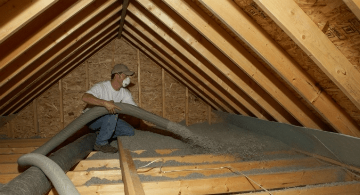 Inside a pitched roof, a man with a face mask blows insulation into the building's rafters.
