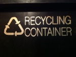 Recycling symbol with 'RECYCLING CONTAINER' gold embossing on black plastic