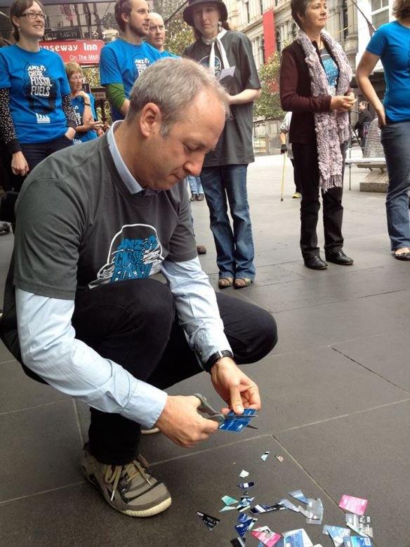 Mature man cutting up ANZ bank card, Melbourne, October 2013