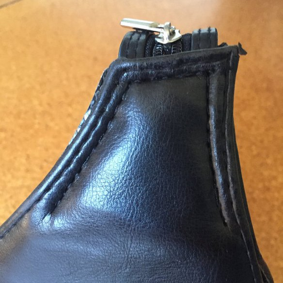 Stitching where zip strap reattached to black bag