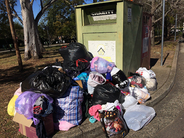 Bags of clothes dumped beside a charity bin