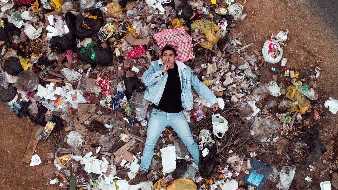 man laying in pile of plastic