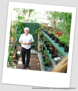 Man in white t-shirt standing next to his vertical rows of potted food plants