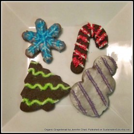 four decorated gingerbread cookies, shaped as a snowflake, candy cane, Christmas tree and snowman