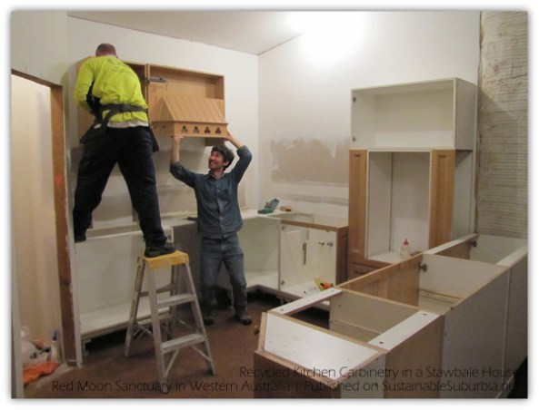 Installing overhead cabinets in a Recycled Kitchen