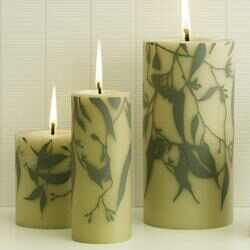Three lit candles with a hand painted gum leaf design.