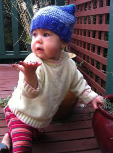 "One year old Eliane modelling her square beany, and holding up for hand as if to say ""what""?"