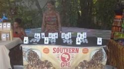 Southern Girl Granola Owner, Erika Benjamin stands radiant with her products and samples.