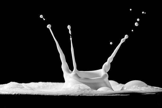 Image of a single drop of milk splashing upwards against a solid black background