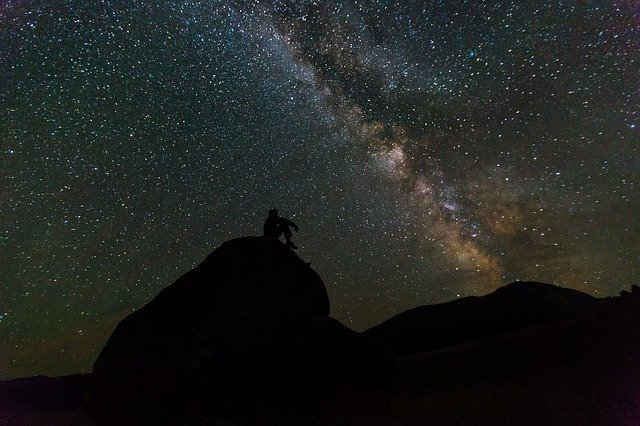 person sitting on a rock outside under a night sky filled with stars
