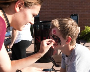 Outside of the Sherratt Library Brooklyn Whitney is putting on the final touches to Jared Brown's zombie makeup. Photo courtesy of photo journalist Morgan Barton.