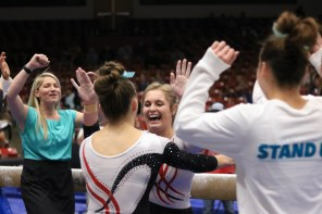 SUU Flippin' Birds wear teal bows in their hair and Set the Expectation shirts. Assistant Coach Jamie Wysong also wears teal for the March 3 meet. Photography by Easton Bowring