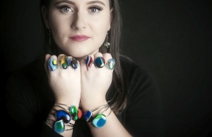 Model wearing a variety of glass rings and bracelets
