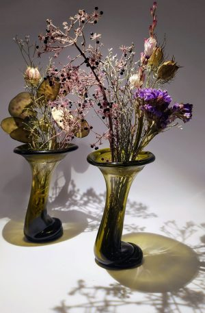 a pair of vases with dried flowers. Each vase is made from recycled glass