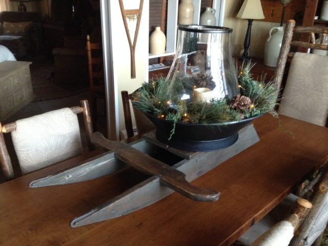 In a large metal bowl, add a large glass chimney, some greens and a candle. Mix well and place on an old handcrafted sled. Voila! You have a wonderful holiday centerpiece. After the holiday, simply re-mix and match other items.