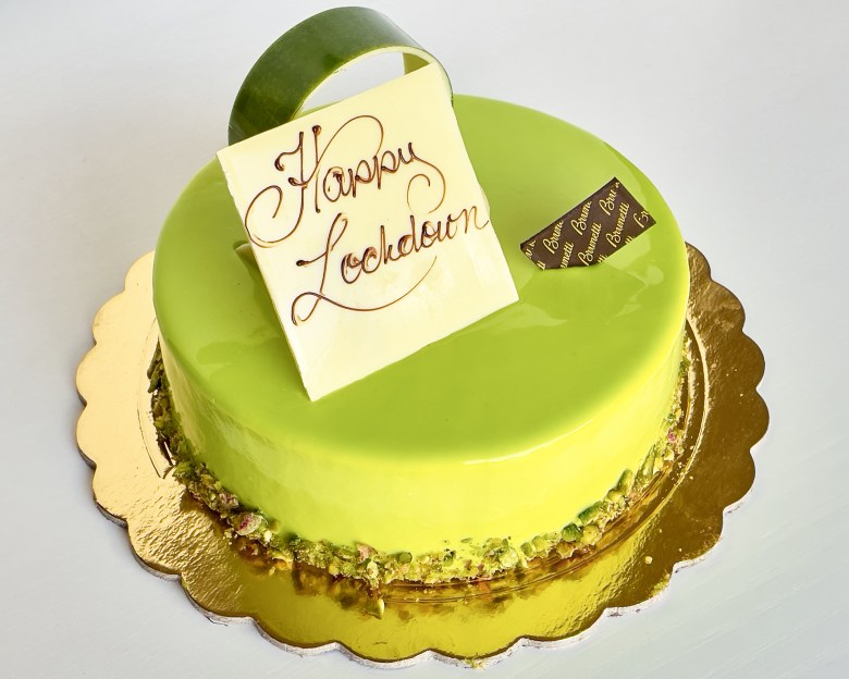 Green cheesecake on gold board with Happy Lockdown white chocolate plaque