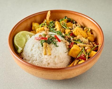 Brown bowl with turmeric tofu, rice, crispy greens and a lime wedge