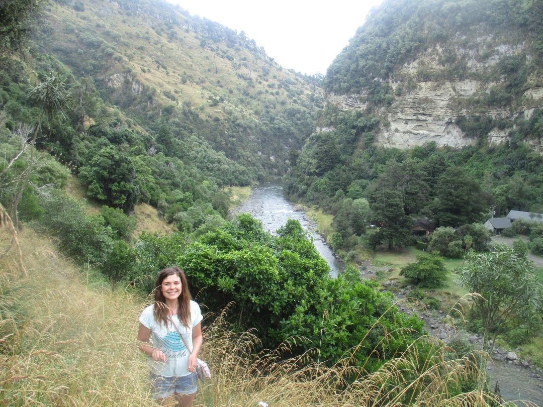Woman smiling along a narrow and steep walk along the river in North Island New Zealand