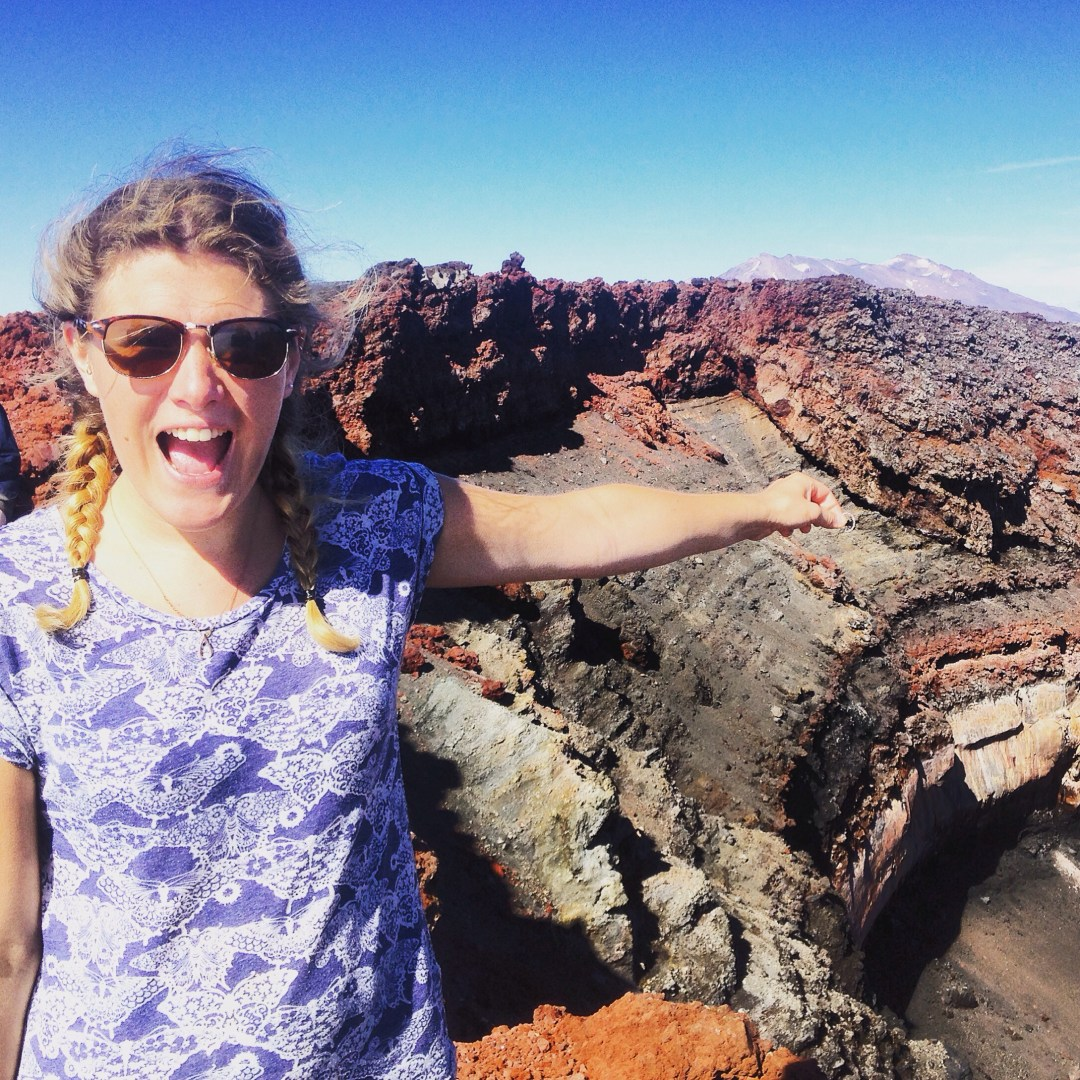 Suzy stands smiling with arm outstretched with a ring in her hand pretending to throw it into the crater of Mount Doom