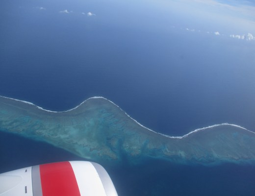 Plane window view over the Pacific Ocean flying between Auckland NZ and Nadi Fiji where corals and islands provide stunning views