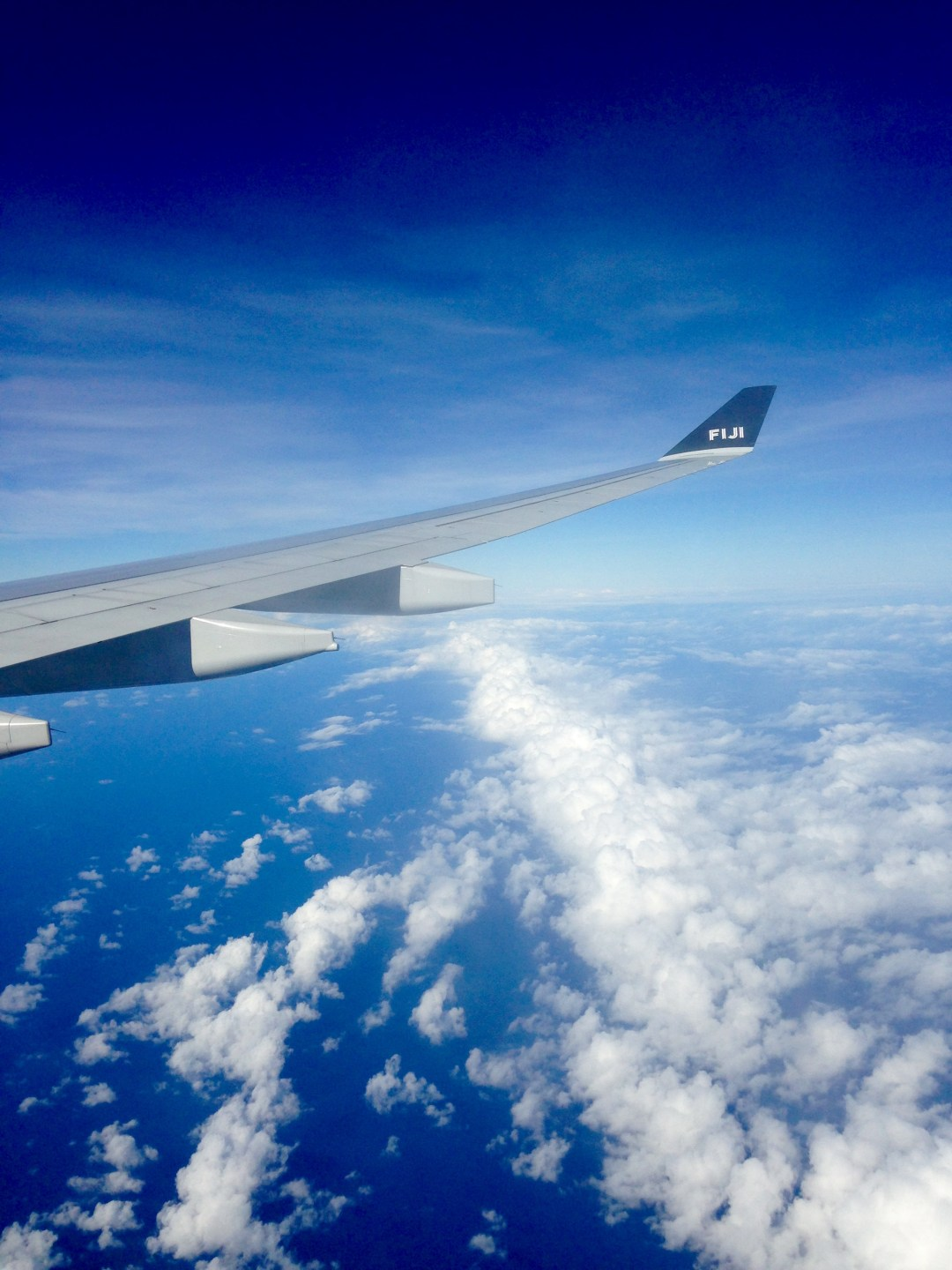 Blue skies and blue waters with a plane wing in full view on a flight from Nadi Fiji to Cairns Australia with Fiji Airways