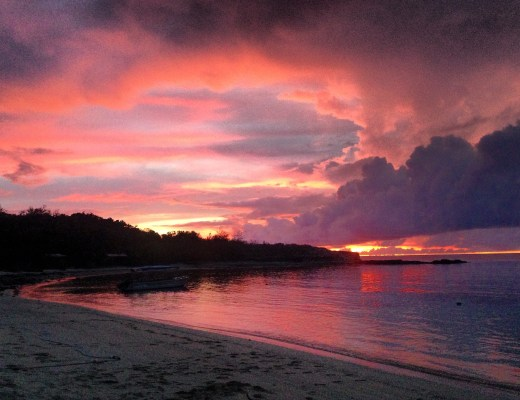 A fiery purple and pink sunset over still waters and beach on an island in Fiji