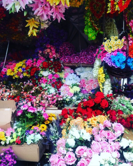 Bright coloured flowers tightly packed together in a market stall