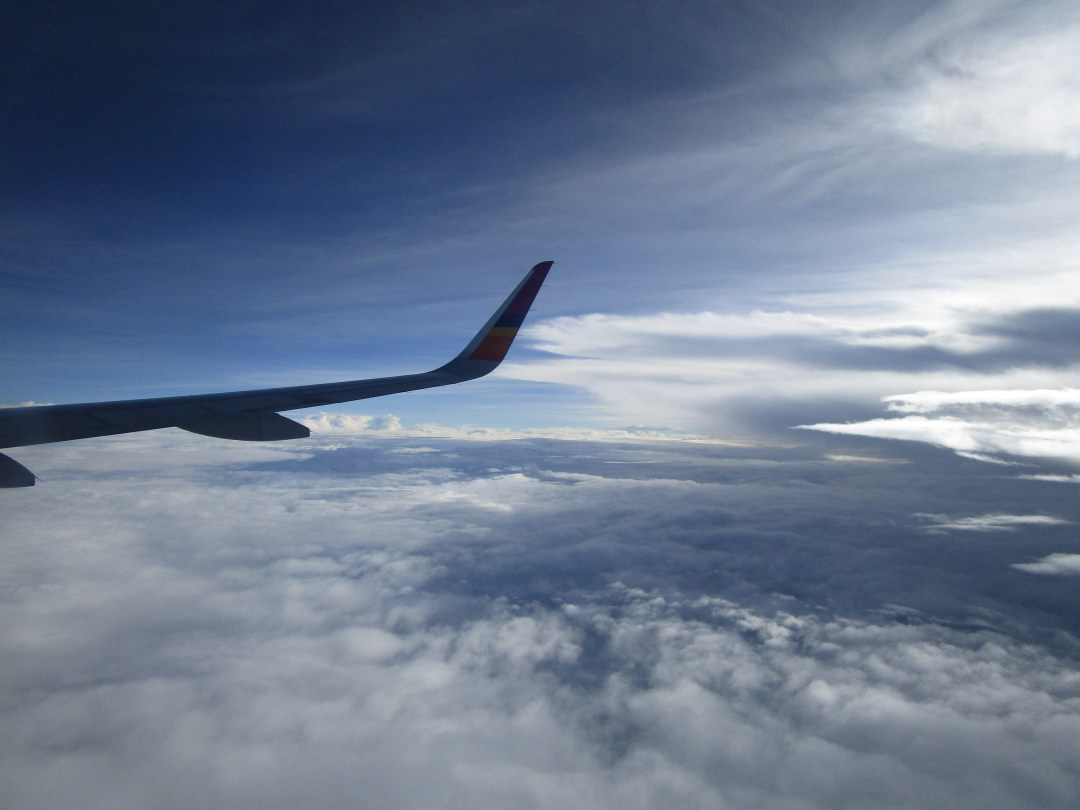 view over clouds and plane wing in flight