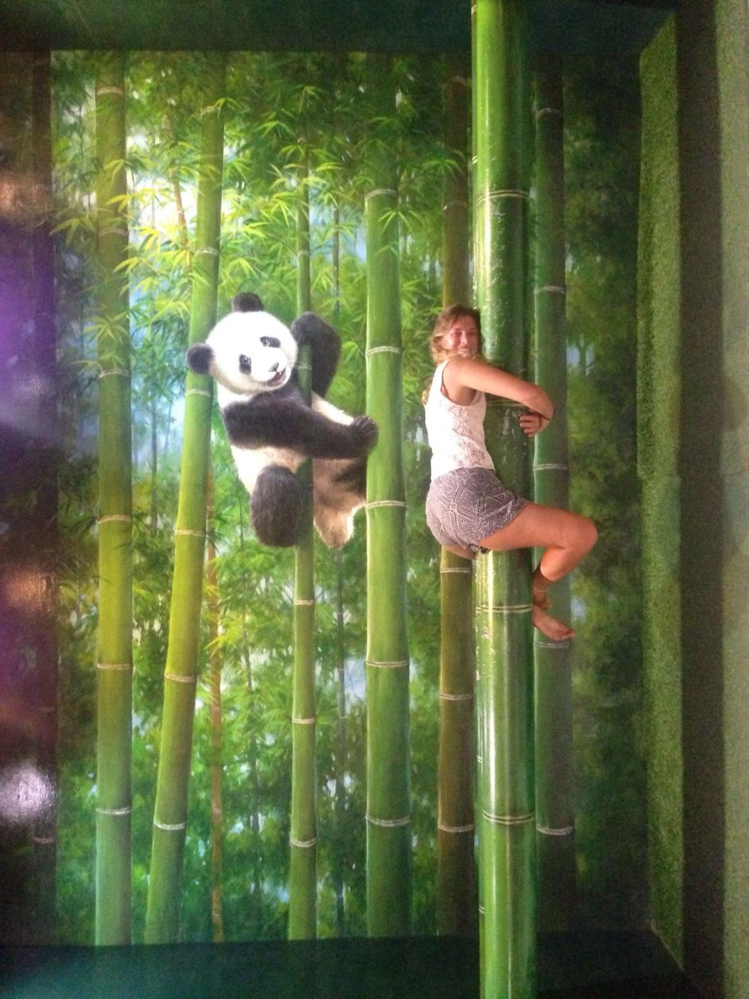 Art piece flipped on its side to pretend girl climbing a bamboo tree