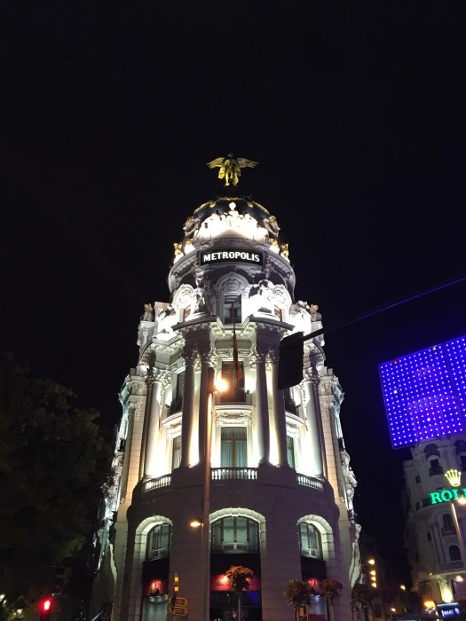 The illuminated Metropolis Building at night in Madrid