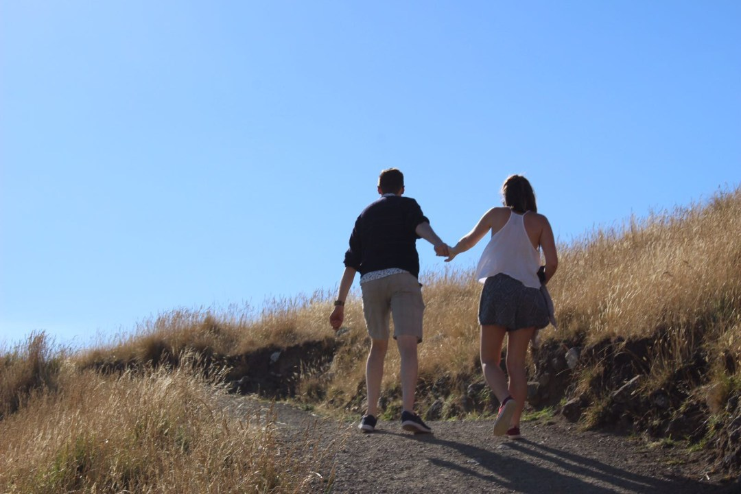 couple hand in hand walk up hill
