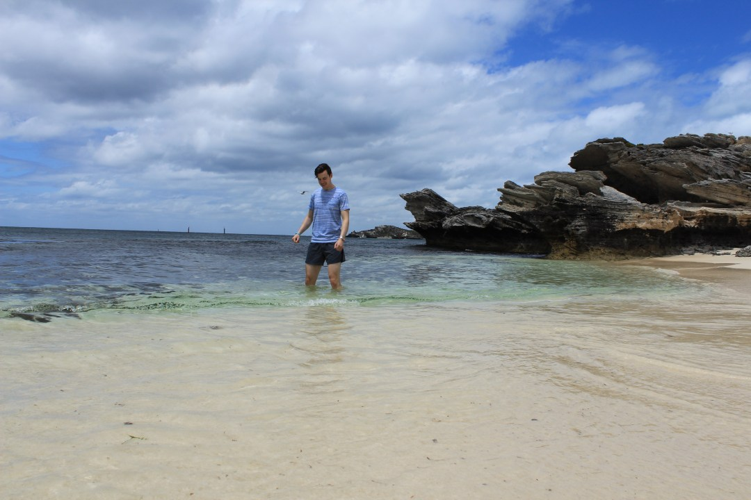 Man enjoys a paddle in shallow beach waters
