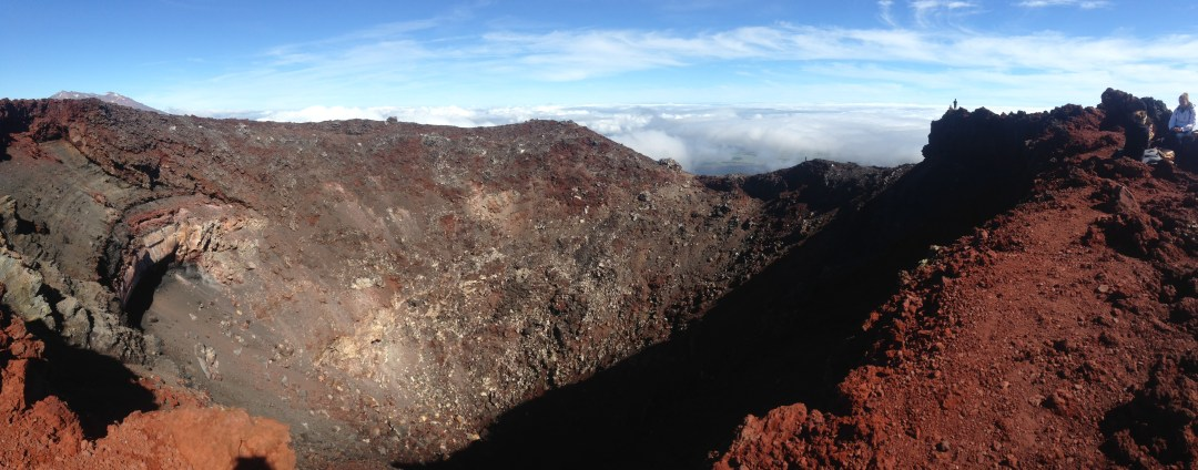 At the top of Mount Doom we see the red rocks around the deep crater ahead