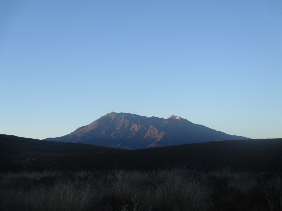 Mount Doom stands tall with the early sunrise light shining down