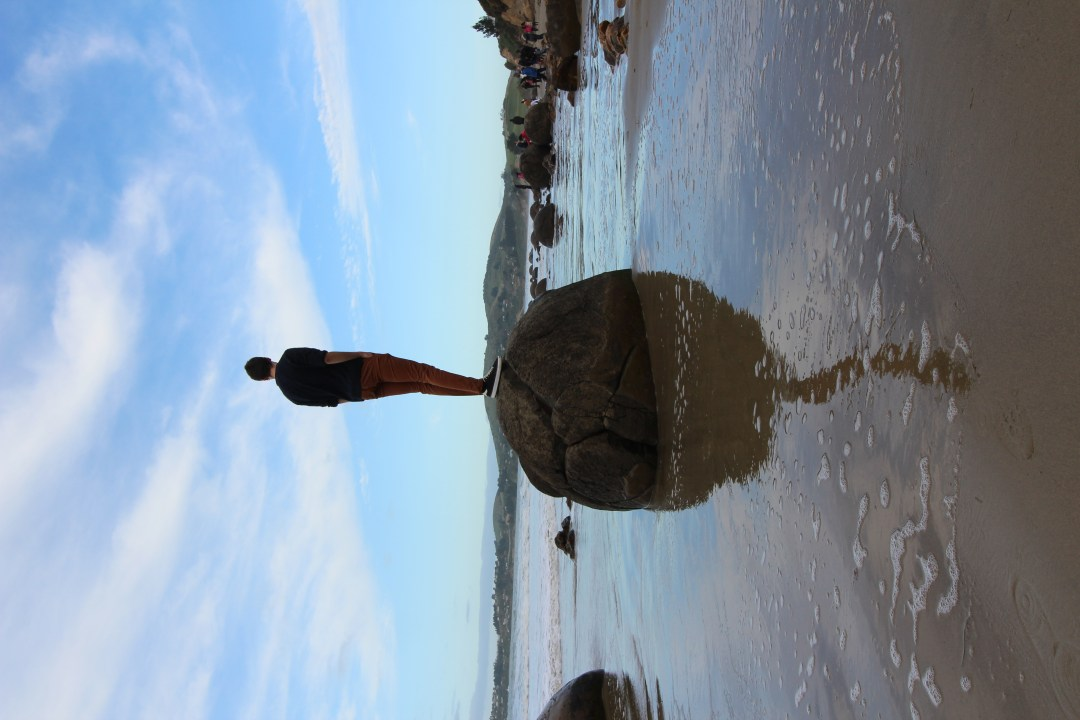 Man stands on top of Moeraki Boulders showing reflection in the water